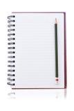 Cahier sur le blanc avec des crayons. Photo libre de droits