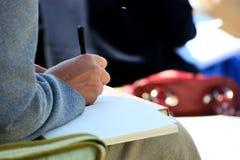 Cahiers et écriture de contact de conférence Photo stock
