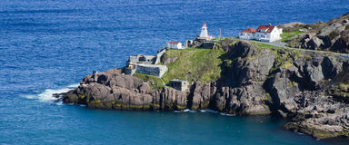Cahill Point, St. John's, Canada. The lighthouse and lightkeeper buildings on the rugged coastline at Cahill Point, the entrance to the bay of St. John's in Royalty Free Stock Image