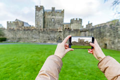 Cahir castle courtyard. Tourist taking a photo of Cahir castle with smartphone Royalty Free Stock Photo