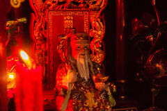 Cai Shen, Chinese God of wealth, God of fortune. Red candle and colorful statue of Cai Shen, Chinese God of wealth, God of fortune, which is a symbol for Royalty Free Stock Photo