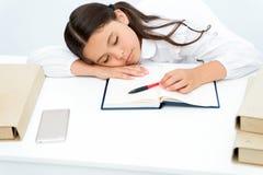 Caia adormecido na lição A criança da menina cair adormecido quando fundo do branco da tabela do livro de leitura Estudante cansa foto de stock royalty free
