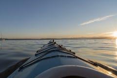 Caiaque do mar do ponto de vista no por do sol Fotografia de Stock