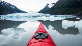 Caiaque vermelho que flutua entre os iceberg que olham para uma geleira no Al Foto de Stock