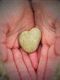 Caillou en forme de coeur dans des mains d'un enfant Image libre de droits