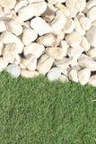 Cailloux blancs contre un bord herbeux images libres de droits