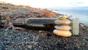 Cailloux de grand dans bouteille la petite et de vin à la plage de bord de la mer Photographie stock