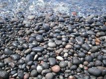 Cailloux de la plage noire de Santorini Images libres de droits