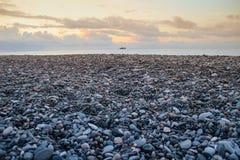 Cailloux gris de mer sur le bord de la mer et le coucher du soleil jaune image stock