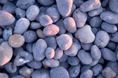 Cailloux gris sur la plage au coucher du soleil avec le coucher du soleil rose de grom de lueur dessus ainsi Photos stock