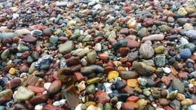 Cailloux multicolores à la plage Lissez des vagues croulantes photos libres de droits