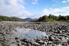 Cailloux sur le rivage d'une rivière Photos stock
