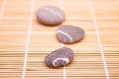 Cailloux sur un tapis en bambou Photos stock
