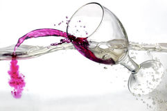 Caindo um vidro do vinho vermelho na água Fotos de Stock Royalty Free