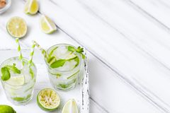 Caipirinha, κοκτέιλ mojito με τον ασβέστη, καφετιά φύλλα ζάχαρης, πάγου και μεντών στα όμορφα γυαλιά, πράσινα εσπεριδοειδή περικο Στοκ Φωτογραφίες