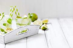 Caipirinha, κοκτέιλ mojito με τον ασβέστη, καφετιά φύλλα ζάχαρης, πάγου και μεντών στα όμορφα γυαλιά, πράσινα εσπεριδοειδή περικο Στοκ Εικόνα
