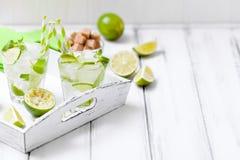 Caipirinha, κοκτέιλ mojito με τον ασβέστη, καφετιά φύλλα ζάχαρης, πάγου και μεντών στα όμορφα γυαλιά, πράσινα εσπεριδοειδή περικο Στοκ εικόνα με δικαίωμα ελεύθερης χρήσης