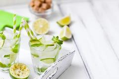 Caipirinha, κοκτέιλ mojito με τον ασβέστη, καφετιά φύλλα ζάχαρης, πάγου και μεντών στα όμορφα γυαλιά, πράσινα εσπεριδοειδή περικο Στοκ Φωτογραφία