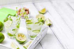 Caipirinha, κοκτέιλ mojito με τον ασβέστη, καφετιά φύλλα ζάχαρης, πάγου και μεντών στα όμορφα γυαλιά, πράσινα εσπεριδοειδή περικο Στοκ φωτογραφία με δικαίωμα ελεύθερης χρήσης