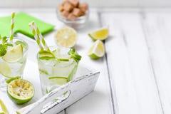 Caipirinha, κοκτέιλ mojito με τον ασβέστη, καφετιά φύλλα ζάχαρης, πάγου και μεντών στα όμορφα γυαλιά, πράσινα εσπεριδοειδή περικο Στοκ εικόνες με δικαίωμα ελεύθερης χρήσης