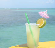 Caipirinha drink in boat support with a blue sea background on a beautiful sunny day Royalty Free Stock Photos