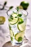 Caipirinha, Mojito cocktail, vodka or soda drink with lime, mint and straw on sand background. Still life. Copy space royalty free stock images