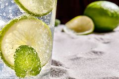 Caipirinha, Mojito cocktail, vodka or soda drink with lime, mint and straw on sand background. Close-up. Caipirinha, Mojito cocktail, vodka or soda drink with royalty free stock images