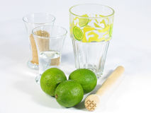 Caipirinha Set I. A caipirinha set with limes, a pestle, one glass with white rum and one with brown suggar and a special Caipirinha glass Stock Image