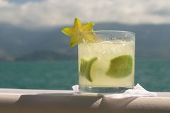 Caipirinha with Star Fruit. Caipirinha (cocktail) with star fruit garnish, with beautiful blue-green water and hills in the background Stock Image