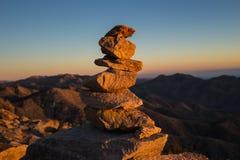 Cairn avec des montagnes à l'arrière-plan au coucher du soleil Photographie stock libre de droits