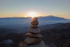 Cairn avec des montagnes à l'arrière-plan au coucher du soleil Image stock