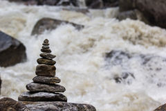 Cairn in the background of swirling river. Stock Photos