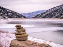 Cairn de roche devant le lac congelé Photographie stock