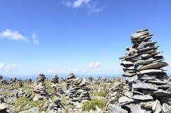 Cairn di pietra con il fondo del cielo blu e dell'erba Immagine Stock