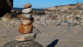 Cairn di pietra impilato sulla spiaggia fotografia stock libera da diritti