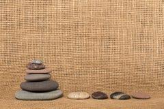 Cairn e pietre di pietra sul fondo della tela da imballaggio Fotografia Stock Libera da Diritti