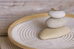 Cairn en pierre avec la plume dans la cuvette en bambou image stock