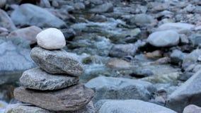 Cairn en pierre près d'une rivière banque de vidéos
