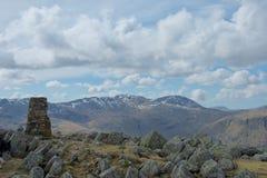 Cairn et roches au sommet de la montagne de secteur de lac ; la neige a couvert des rochers dans la distance photographie stock