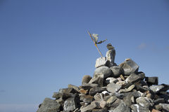 Cairn with Flag against Blue Sky Stock Image