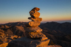 Cairn with mountains in the background at sunset Royalty Free Stock Photography