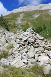 Cairn in the Mountains. A pile of stones on the trail high in the Pirin mountains, Bulgaria. Vihren peak in the background Stock Photos