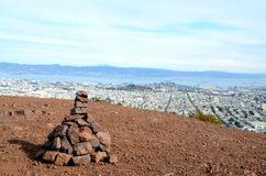 A cairn overlooking San Francisco from Twin Peaks. A stone cairn (stacked rocks) on a trail at Twin Peaks, a popular tourist destination overlooking San Stock Photo