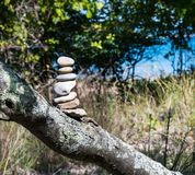 Cairn or Pile of Seven Stones Marking the Trail. Seven stones balanced or piled on top of a tree limb setting on a bluff above a sandy beach on a sunny afternoon royalty free stock image