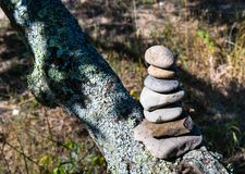 Cairn or Pile of Seven Stones Marking the Trail. Seven stones balanced or piled on top of a tree limb setting on a bluff above a sandy beach on a sunny afternoon stock photo
