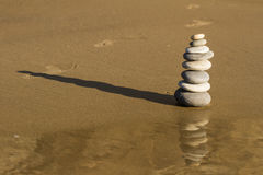 Cairn reflected in wet sand with bare foot prints Royalty Free Stock Photos