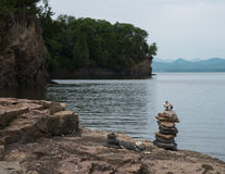 Cairn, stacked stones, on lake shore Royalty Free Stock Images