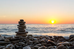 Cairn stones on the beach on sunset. Stacked stones on the stony beach on sunset stock photography