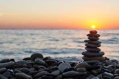 Cairn stones with sun on the beach on sunset. Cairn stones stacked with sun on the stony beach on sundown royalty free stock photo