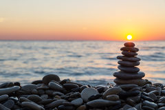 Free Cairn Stones With Sun On The Beach On Sunset Royalty Free Stock Photo - 92648195